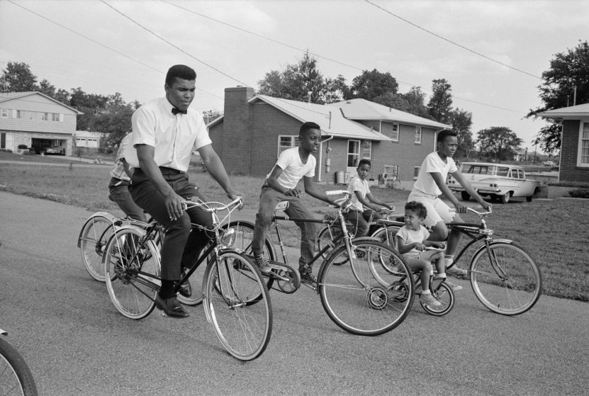 ca. 1963, Louisville, Kentucky, USA --- Cassius Clay, soon to be known as Muhammad Ali, bicycles near his parents' house in Louisville, Kentucky. --- Image by © Steve Schapiro/Corbis